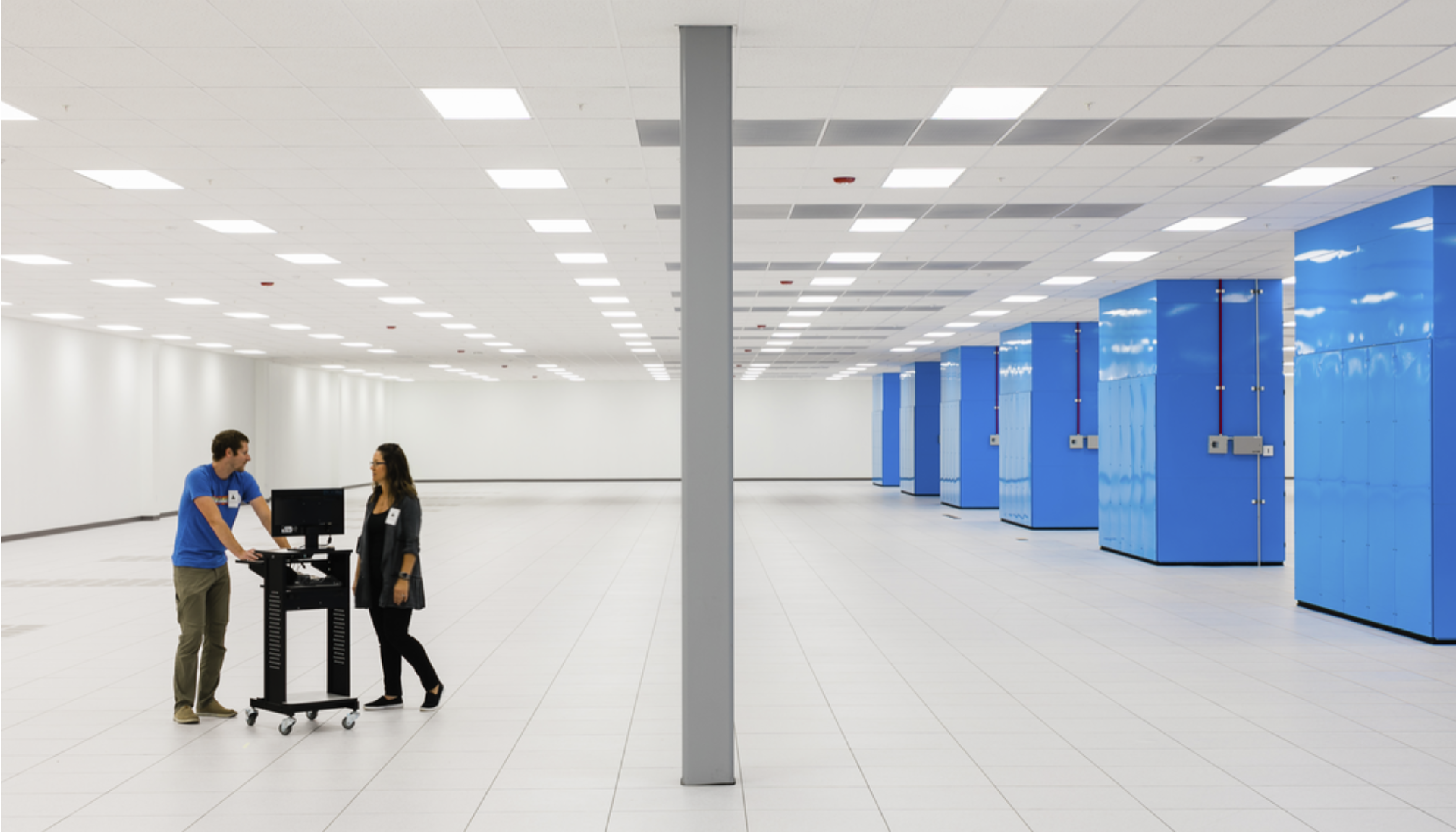 Two people stand in a data center room.