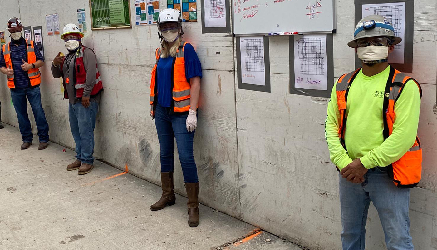 Jobsite workers wear face mask and practice social distancing.