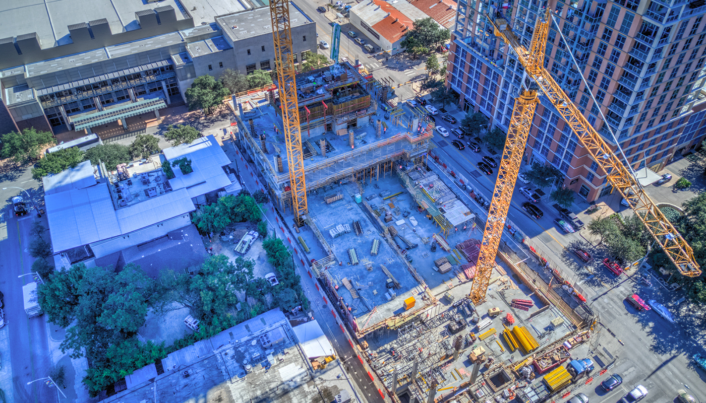 Aerial view of a construction site showing two cranes and tall buildings.