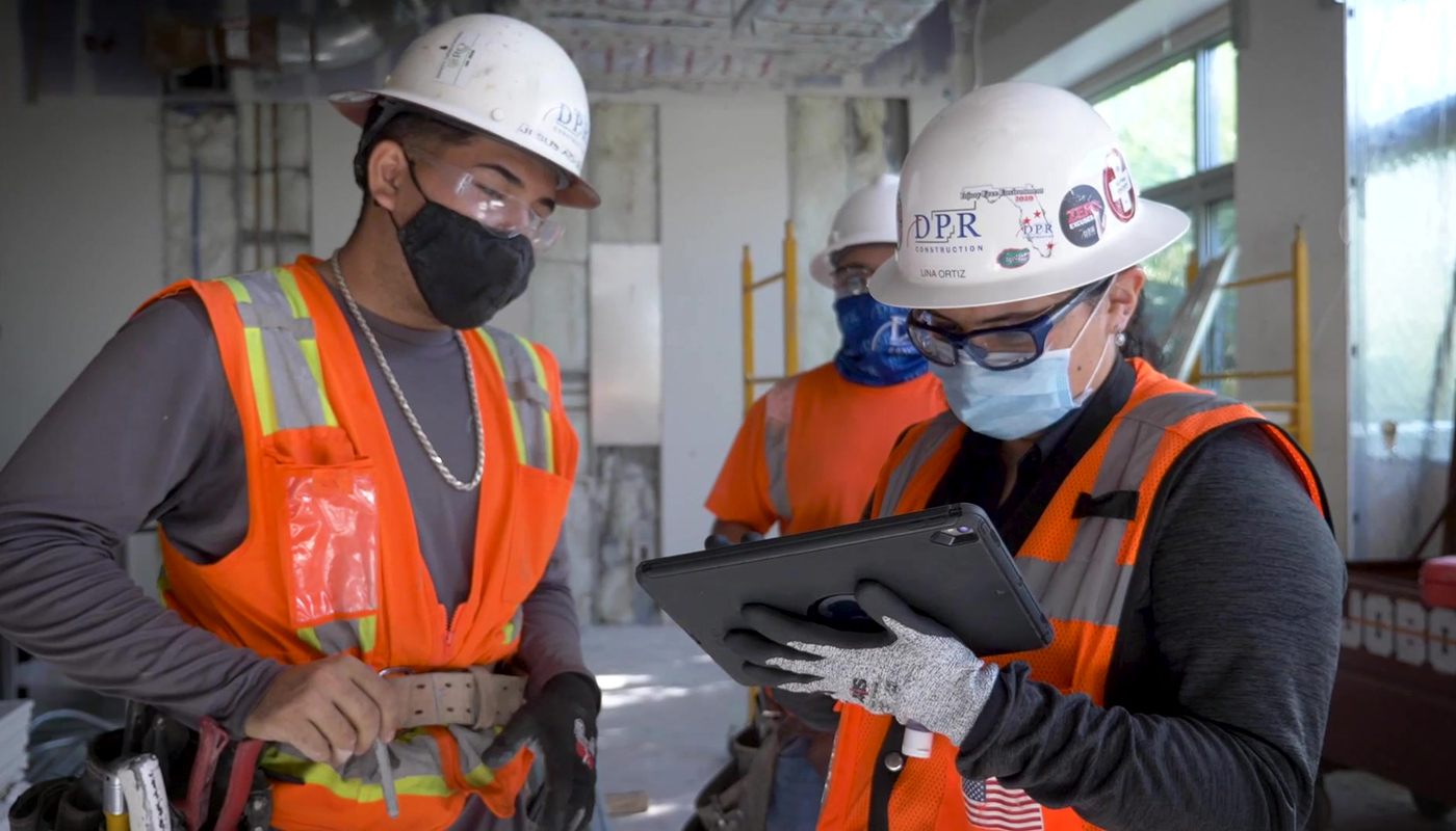 Two people consult at a building app on iPad while working on a construction site.