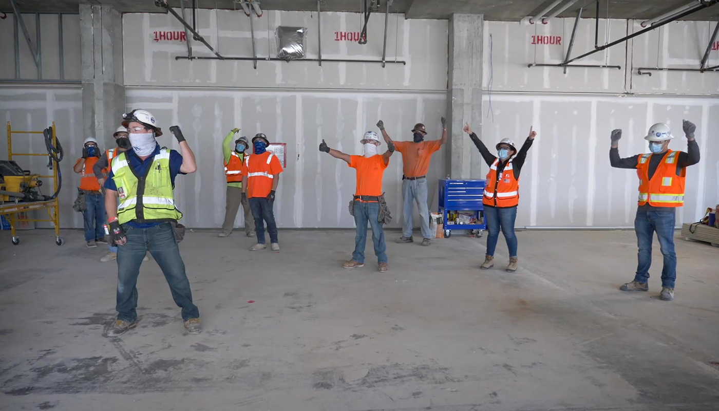 A group of construction workers take part in a stretch and flex exercise at a jobsite.
