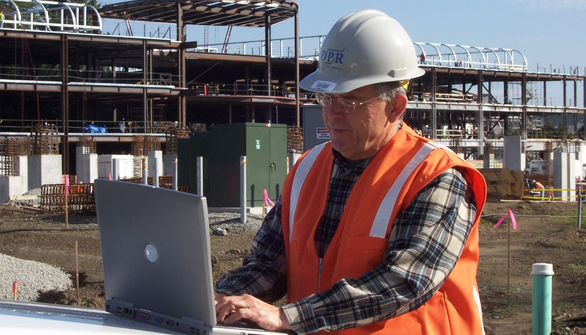 Dean Reed works on his laptop on the hood of a truck from a job site in 2006.