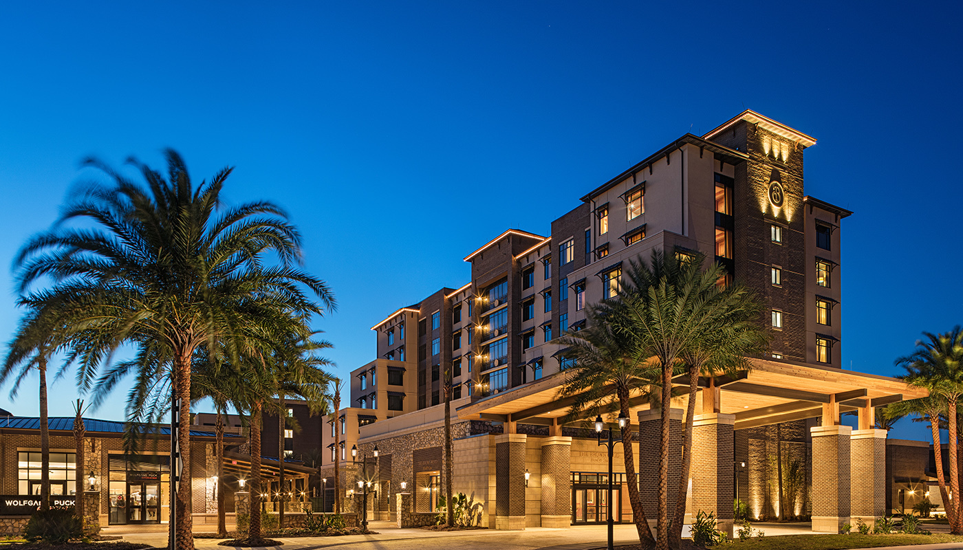 The Brownwood Hotel and Spa building at dusk, flanked by palm trees.