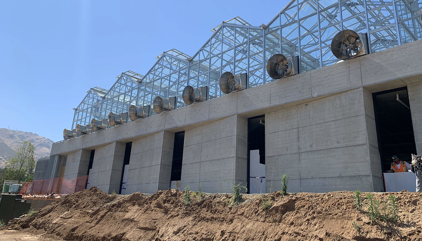 A greenhouse facility mid-construction with a concrete foundation and metal framed second story.