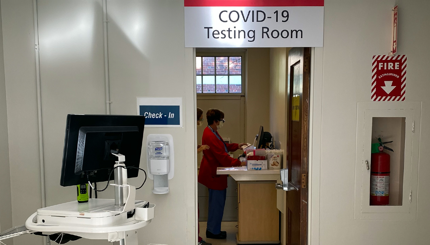 "Hospital hallway with ""COVID Testing Room"" at the end of the hall."