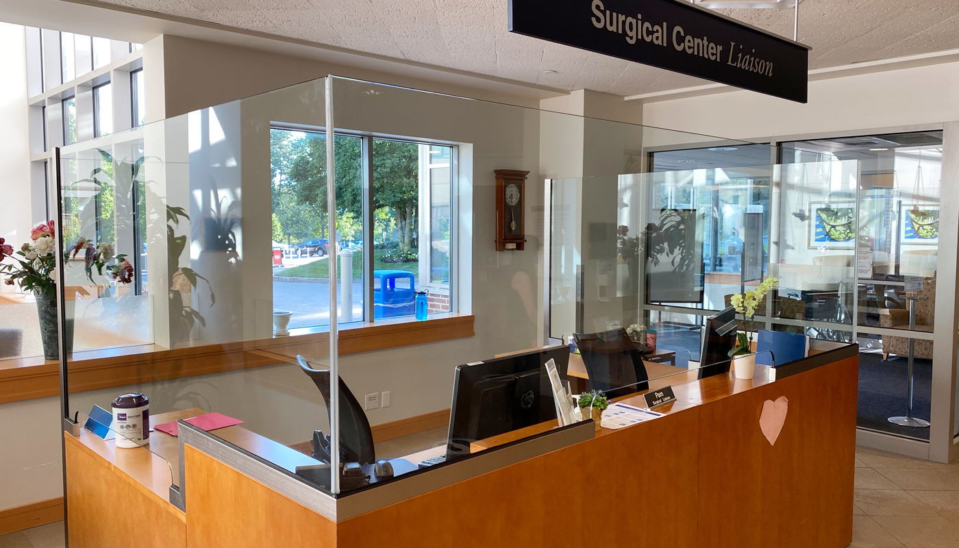 A desk with newly-installed plexiglass inside a healthcare facility.