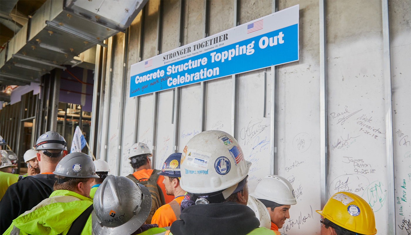 Subcontractors sign the wall, leaving their mark on the project during the concrete topping out celebration.