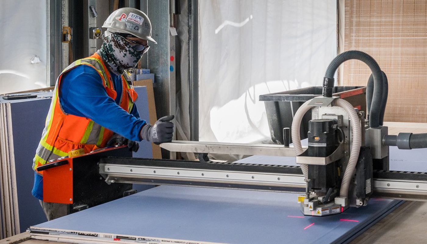 A worker in a facemask uses a machine to cut drywall.
