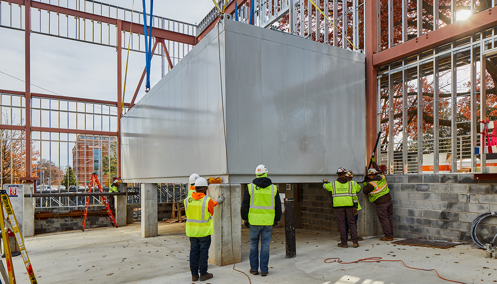 DPR workers finalize installation of a modular unit at the NIH project.