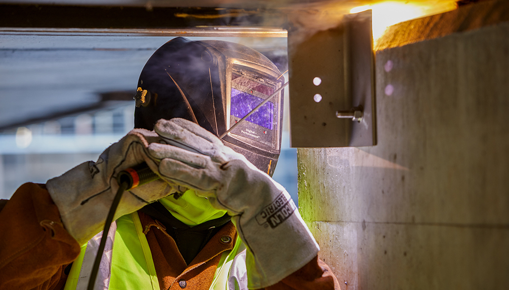 A worker welds at the NIH project
