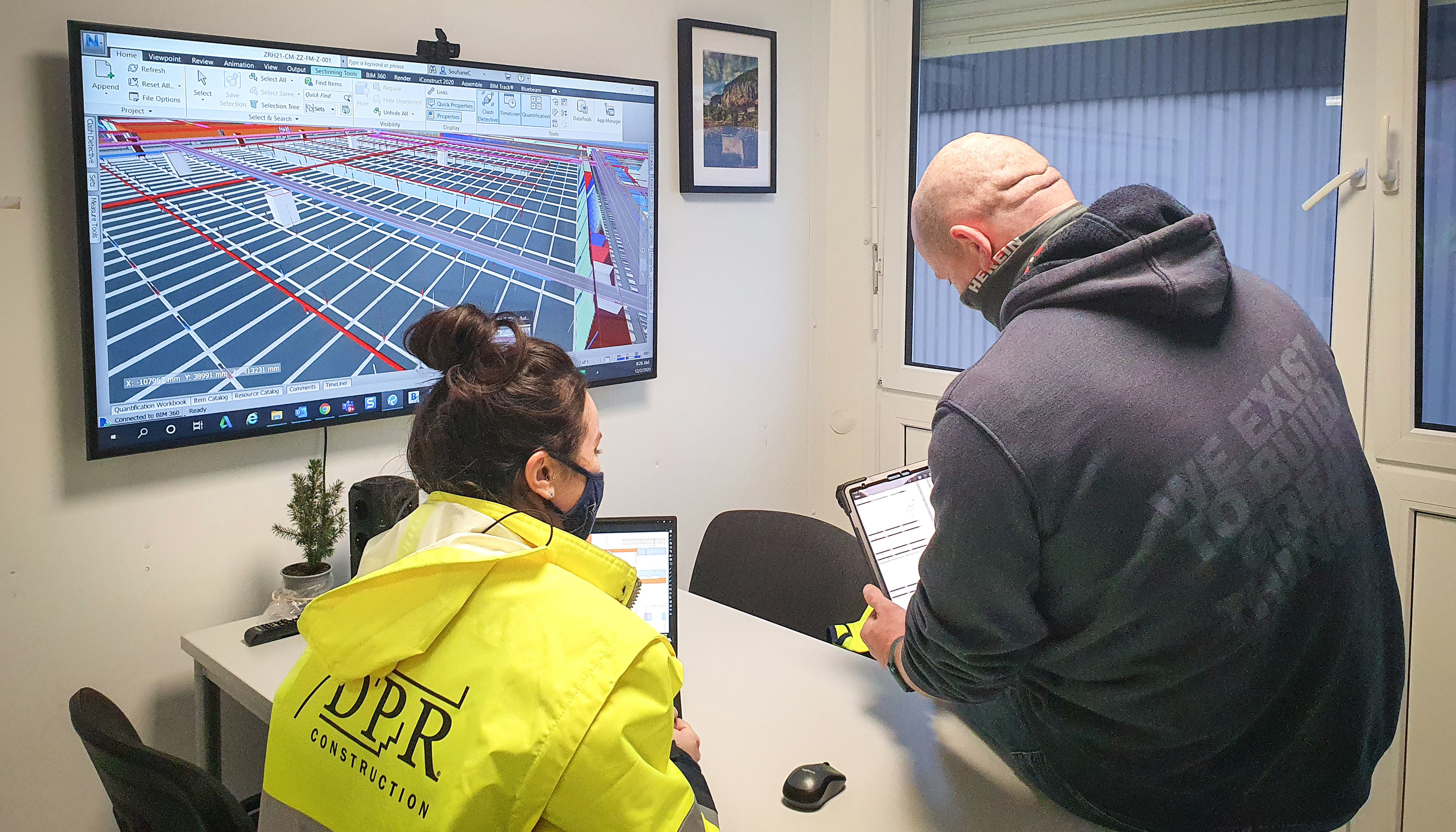 Two DPR workers in a jobsite office review a digital model of their project on a wall-mounted screen.