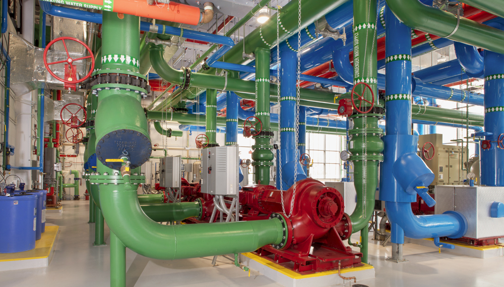 Pipes and ductwork overlapping throughout the interior of the utility plant.