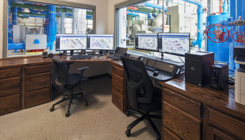 Office space inside the plant where digital models of building systems are shown on screen.