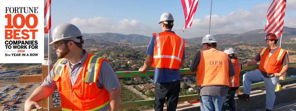 Employees looking out over a construction site. Links through to the careers page.