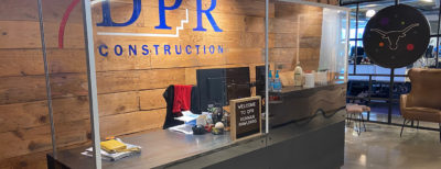 The reception desk at DPR Construction's Dallas office with a newly-installed barrier.