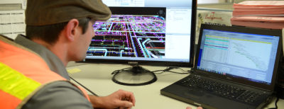 A DPR worker using his desktop computer to use virtual design and construction tools in support of MEP work.