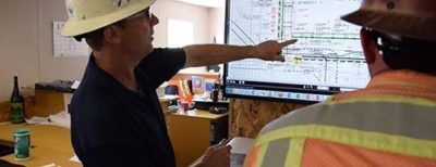 Two DPR workers inside a job site trailer review design drawings.