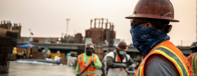 A worker oversees the concrete pour on a jobsite