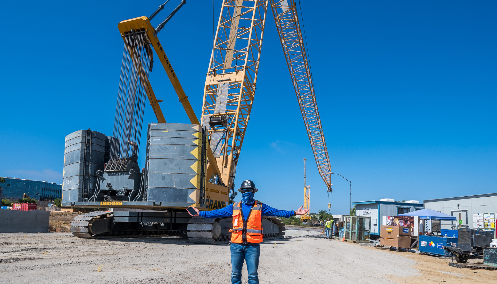 A worker stands in front of a large crane used on a project site in San Diego