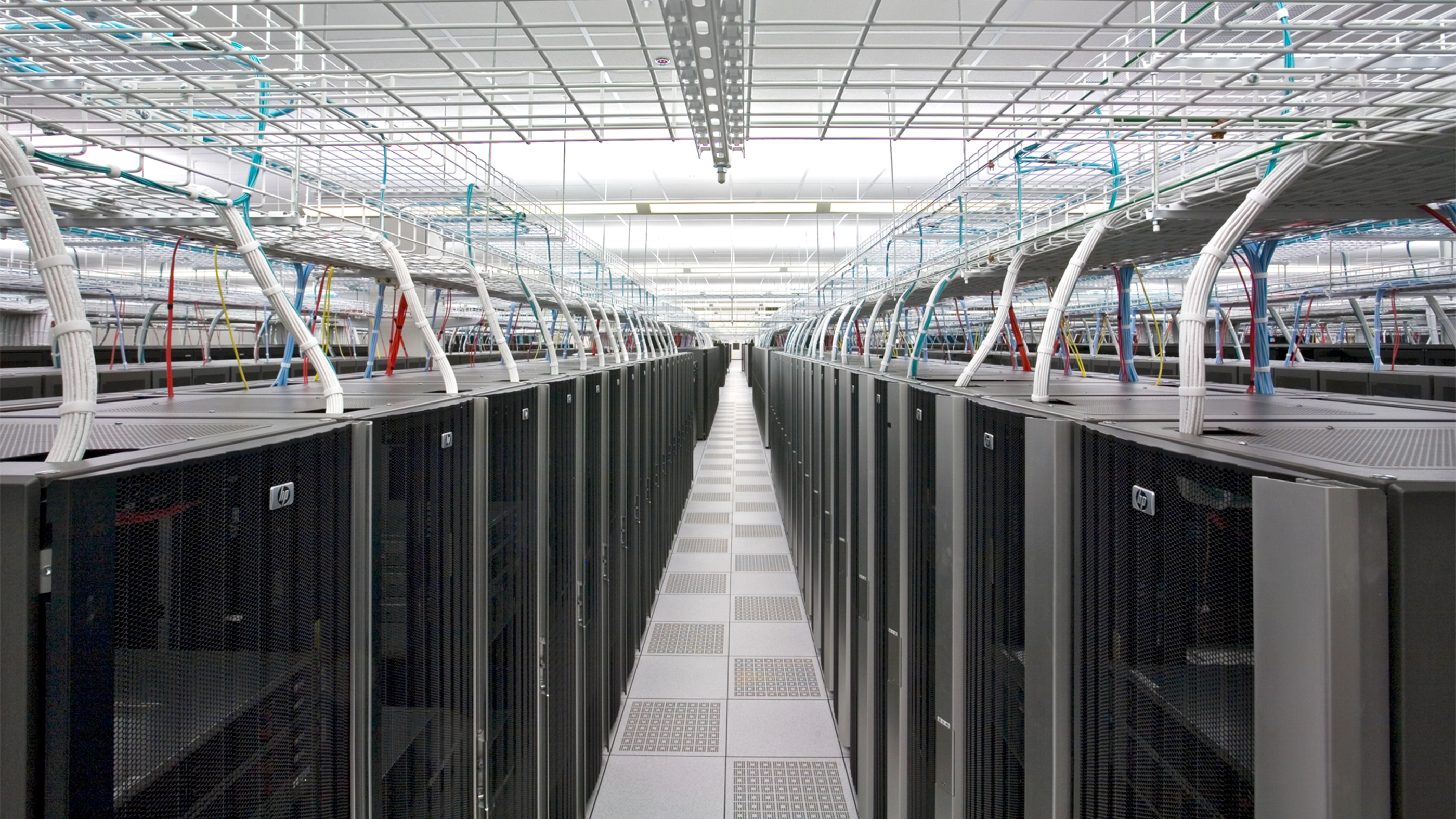 View down a server aisle with organized wiring above the rows.