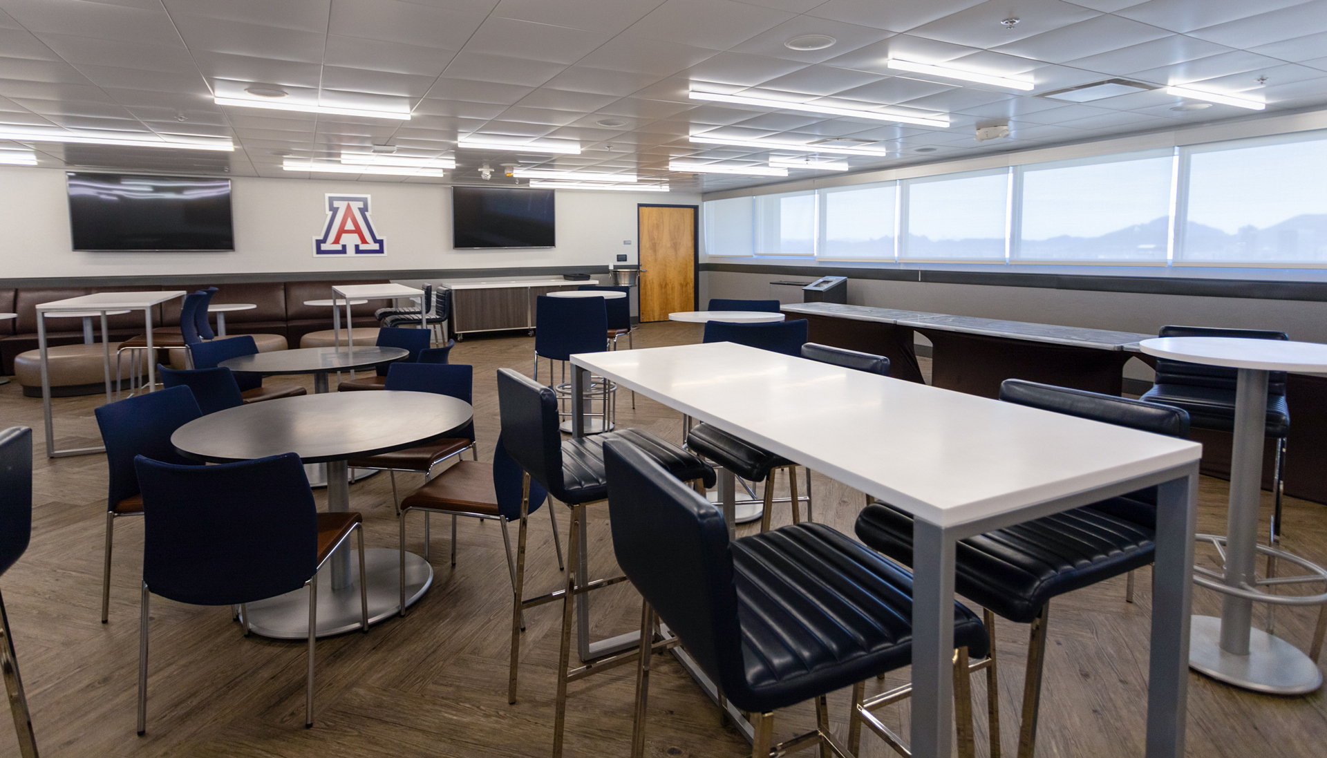 A view of the social area with tables and chairs in the third level Skybox Suites in Arizona Stadium.
