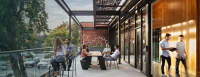 Outdoor patio with people sitting and talking next to an open wall that lets fresh air into a hallway, people walk by inside.