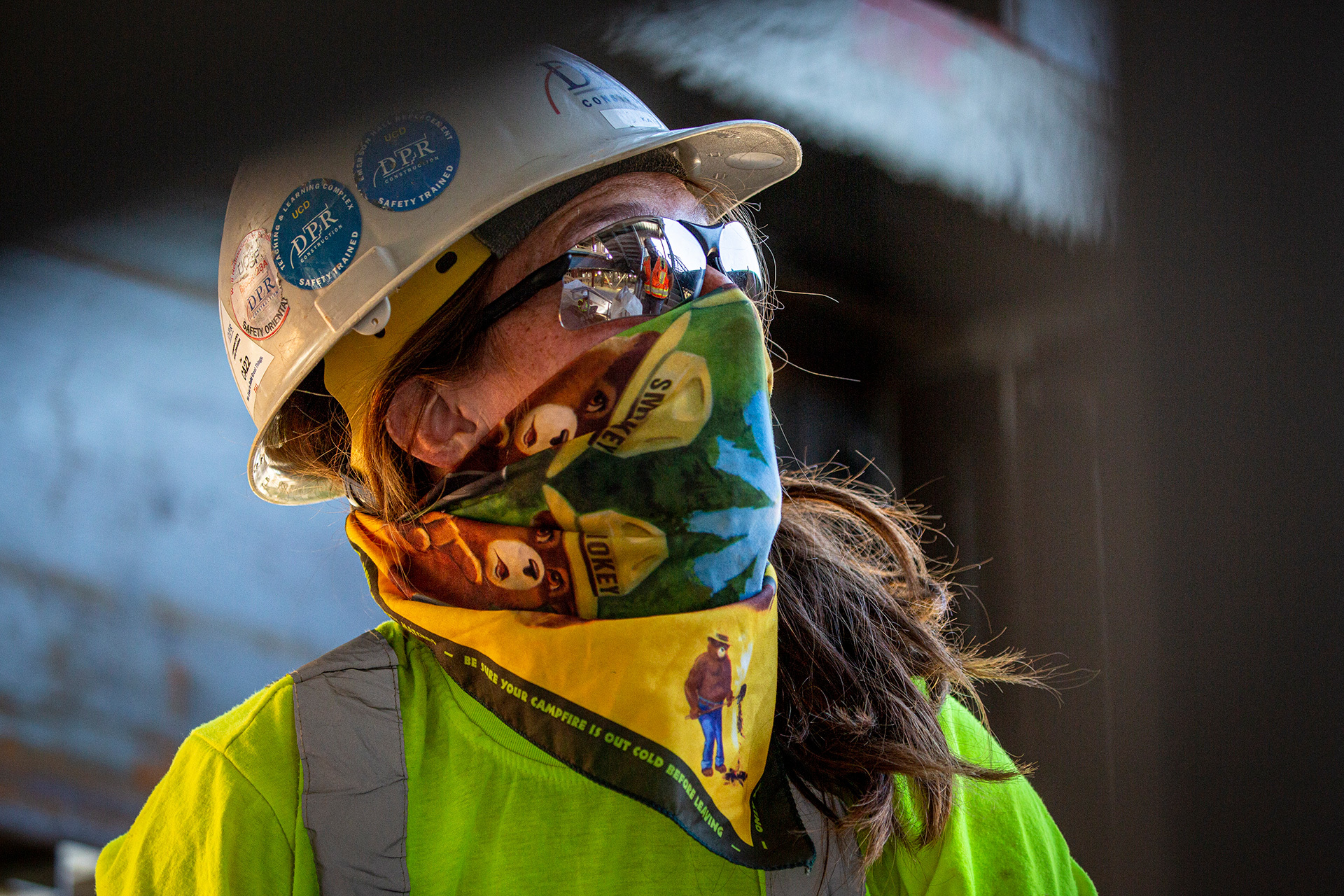 A construction worker wearing a face gator and hard hat