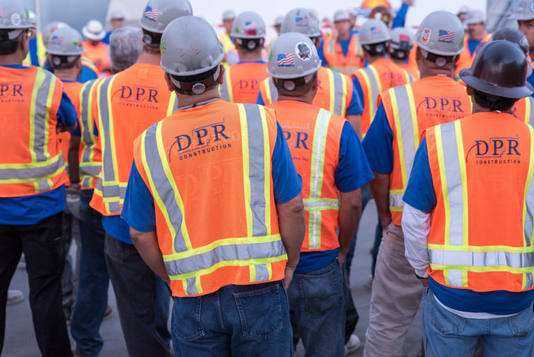Jobsite meeting showing backs of workers wearing safety vests