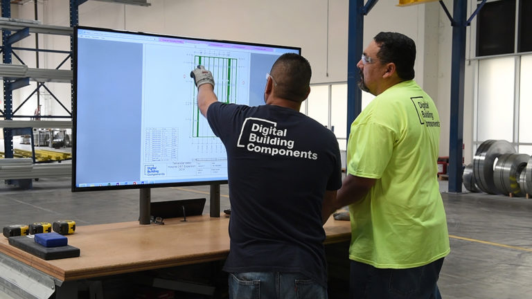 Two workers for Digital Building Components review plans for a prefabricated structure
