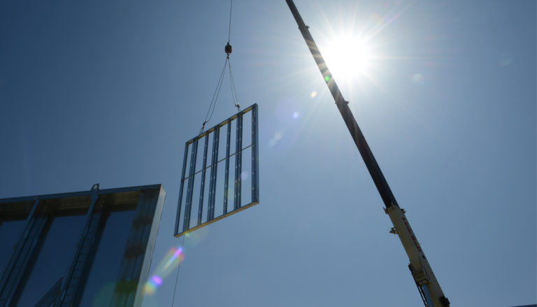 A prefab panel is moved with a crane on a jobsite.