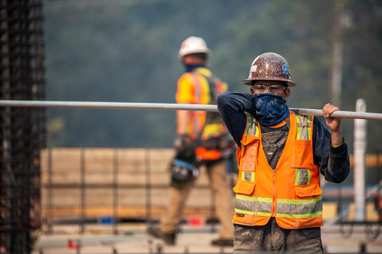 A worker carriers a long bar across his shoulders on a jobsite.