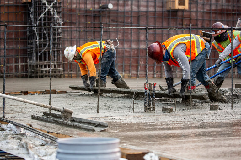 A team of workers spread concrete on a jobsite.