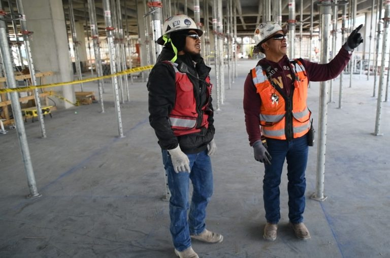 Workers point and look at something above view on a jobsite.