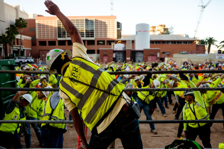 Group of construction workers doing stretching exercises