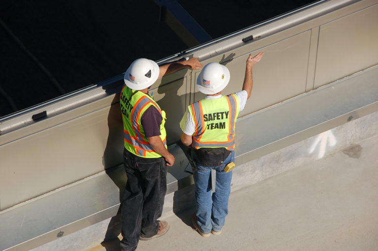 Two workers conduct a safety inspection on a jobsite.