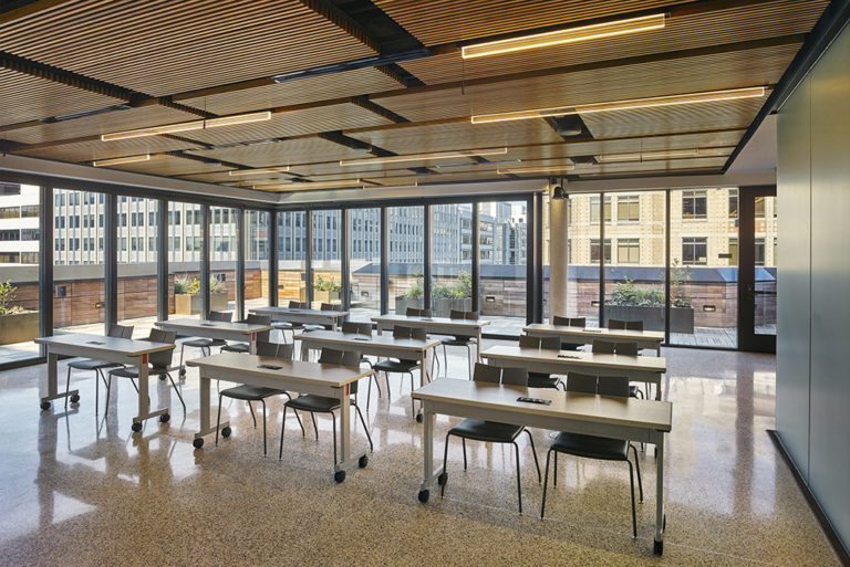 Rows of desks in front of windows on a terrace level classroom