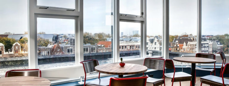 Tables and chairs arranged in an open corner space with walls of windows overlooking Amsterdam.