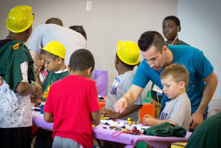 DPR Volunteer assisting children with a fun build project