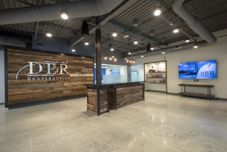 Open lobby with wood accent wall and DPR logo on the wall.