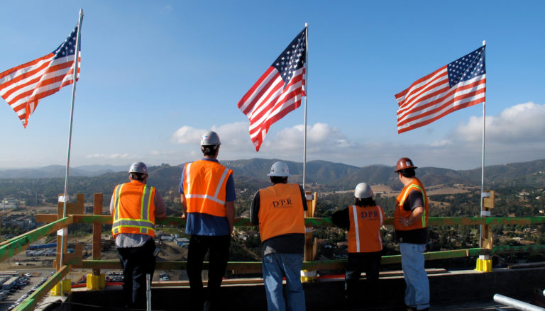 Workers looking at the view from a project, with three flags on railings.