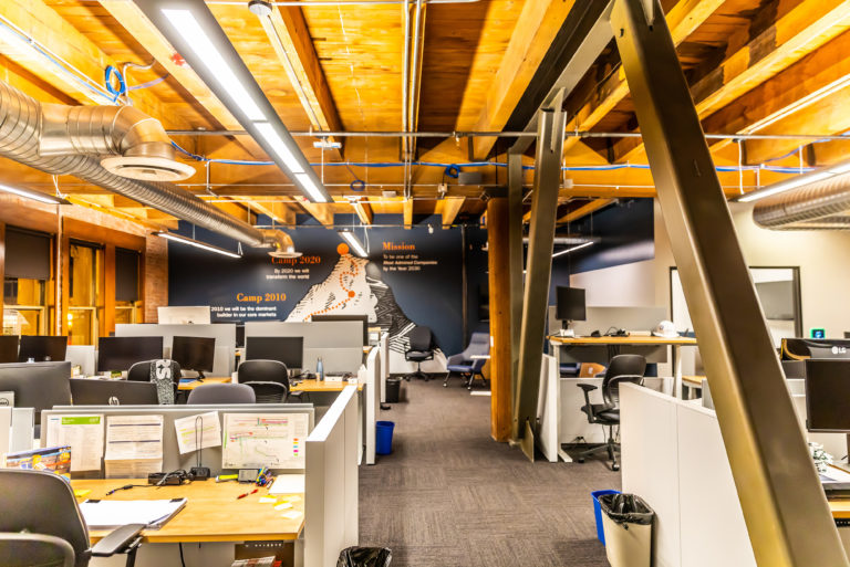 Office interior with exposed wood beam ceiling, workstations and a DPR mountain wall mural.