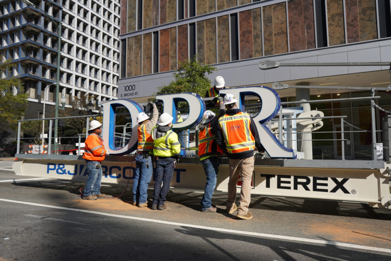 Workers around the DPR letters staged for a crane.