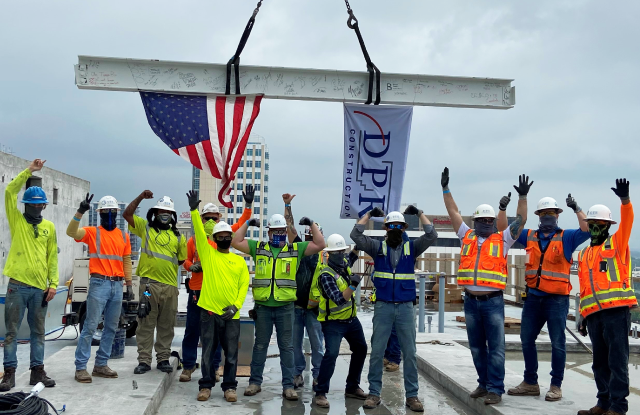 A construction team poses for a topping out photo.