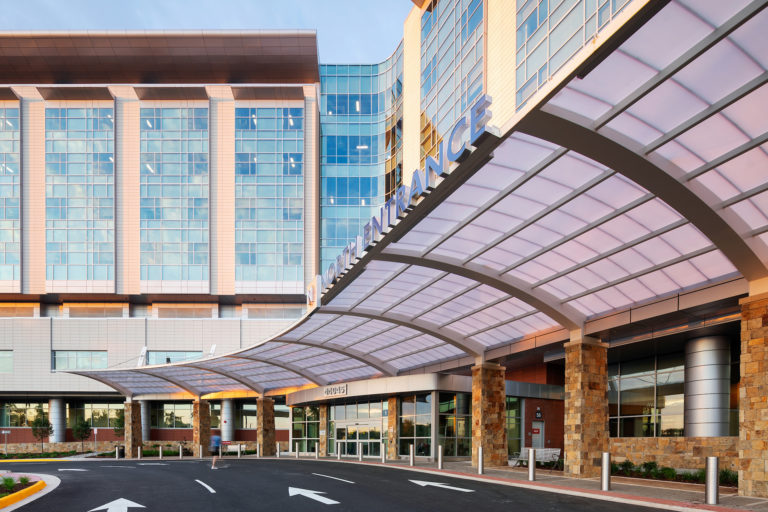 North entrance of hospital building with large overhang over the road.