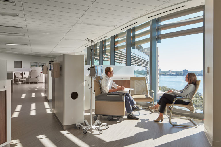A patient and a visitor sit in a calm space next to a sunny window.