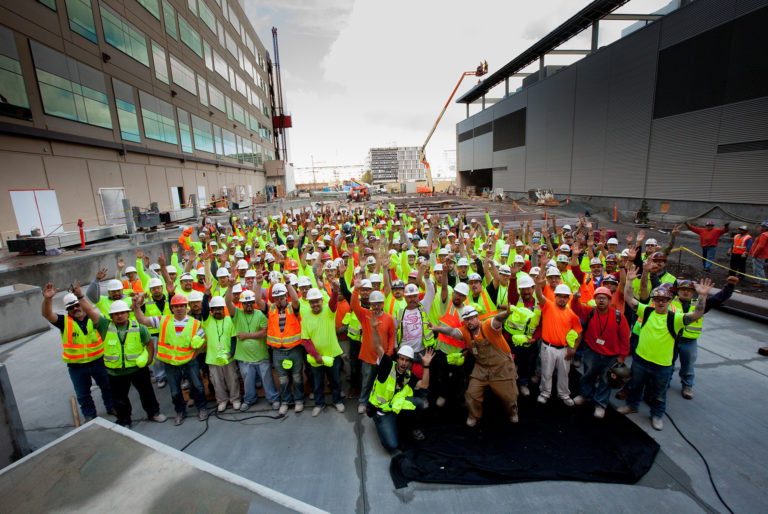 A large team of workers smile and throw their hands in the air for this group job site photo.