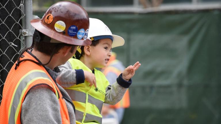 Construction worker father and son in hard hats