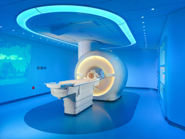 MRI machine in the center of a room lit with blue light.