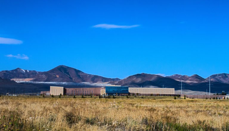 Exterior wide shot of a data center with a mountain range behind the building.
