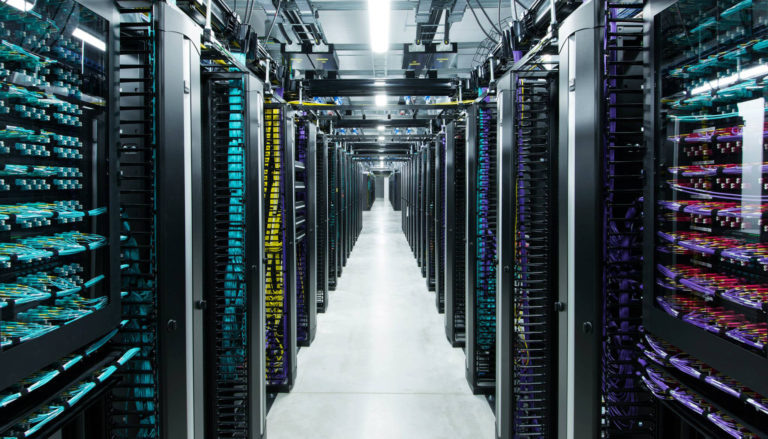 Interior hallway of data center racks and colored cables.